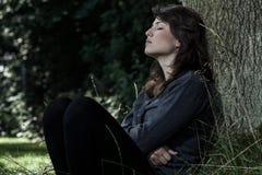坐在树下的哀伤的妇女 免版税图库摄影