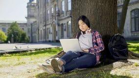 坐在树下的大学生在校园里,使用膝上型计算机,写最后的纸 库存照片