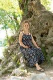 坐在树下的美丽的孕妇 库存图片