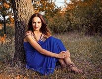 坐在树下的美丽的微笑的女孩 图库摄影