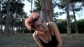 坐在树下的衣领和黑布料的年轻俏丽的被刺穿的女孩在杉木森林里在日落时间 股票视频