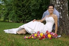 坐在树下的年轻新娘 库存照片