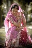 坐在树下的年轻美丽的印地安印度新娘用被举的被绘的手 免版税库存图片
