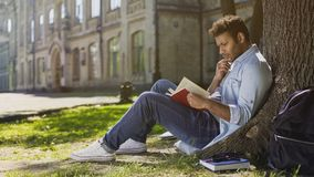 坐在树与扣人心弦的剧情的阅读书下的大学生,大字书写 库存照片