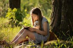 坐在树附近和读书的女孩,拿着拉布拉多小狗 在日落在森林里在夏天 ??  免版税库存图片
