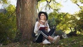 坐在树附近在绿色公园和写某事的帽子和太阳镜的美丽的年轻女人在她的牛奶店 影视素材