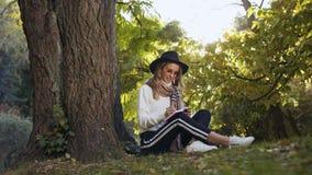 坐在树附近的微笑的妇女公园一会儿做在她的笔记本的某一笔记 股票录像
