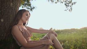 坐在树附近的礼服的女孩,采摘花,唱歌曲 股票录像