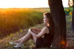 坐在树附近的美丽的轻松的妇女 免版税图库摄影