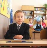 坐在校服的男小学生在教室 库存照片