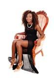 坐在桃红色扶手椅子的美丽的妇女 免版税库存照片