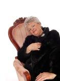 坐在桃红色扶手椅子的资深妇女 免版税库存图片