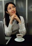 坐在桌上和作梦关于他们的计划的女孩 免版税库存图片