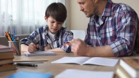 坐在桌上和使他反复无常的儿子的爸爸做家庭作业,教育 股票视频