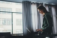 坐在桌上和使用手提电脑的英俊的女性工友 r ?? 免版税库存图片