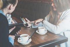 坐在桌上和使用智能手机的两个少妇 显示在智能手机屏幕上的妇女同事图象 库存照片