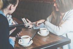 坐在桌上和使用智能手机的两个年轻女商人 显示在智能手机屏幕上的妇女同事图表 免版税库存图片