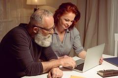 坐在桌上和使用膝上型计算机的丈夫和妻子画象  图库摄影