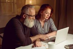 坐在桌上和使用膝上型计算机的丈夫和妻子画象  库存图片