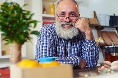 坐在桌上和倾斜他的头的愉快的老人在Th 免版税库存图片