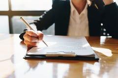 坐在桌上和写在企业合同的女实业家的手在办公室 免版税库存图片