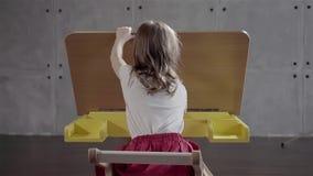 坐在桌上和去掉油漆刷的小女孩 影视素材