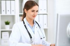 坐在桌上和工作在计算机旁边的拉丁美洲的女性医生在医院办公室 医师或治疗师 库存照片
