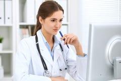 坐在桌上和工作在计算机旁边的拉丁美洲的女性医生在医院办公室 医师或治疗师 免版税库存照片