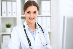 坐在桌上和工作在计算机旁边的拉丁美洲的女性医生在医院办公室 医师或治疗师 图库摄影