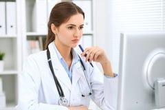 坐在桌上和工作在计算机旁边的拉丁美洲的女性医生在医院办公室 医师或治疗师 库存图片