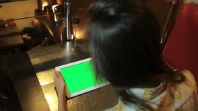 坐在桌上和拿着片剂的妇女填装了绿色 色度钥匙锁上 影视素材
