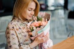 坐在桌上和拿着美丽的玫瑰色颜色花束的女孩 免版税图库摄影