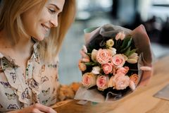 坐在桌上和拿着美丽的花束的女孩 库存图片