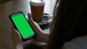 坐在桌上和拿着绿色屏幕巧妙的电话的妇女的手,当食用咖啡时 股票录像