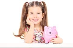 坐在桌上和拿着piggybank的小女孩 图库摄影