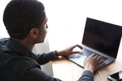 坐在桌上和研究便携式计算机的年轻非洲商人 免版税库存照片