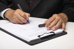 坐在桌上和签署文件的执行委员 免版税库存照片