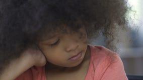 坐在桌上和考虑妈妈的孤独的非裔美国人的女性孩子 股票录像