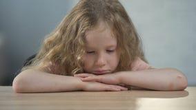 坐在桌上和考虑父母的孤儿女孩在住宿学校 影视素材
