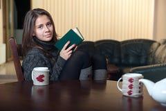 坐在桌上和读书的妇女 免版税图库摄影