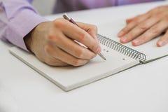 坐在桌上在办公室内部和殷勤地写有些笔记的特写镜头商人在绿色笔记本 库存照片