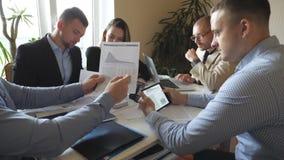 坐在桌上在现代办公室和研究新的项目的小组年轻商人 仔细同事回顾 股票视频