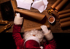 坐在桌上在他的屋子里和读圣诞节信或愿望的圣诞老人 库存图片