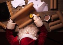 坐在桌上在他的屋子里和读圣诞节信或愿望的圣诞老人 免版税库存图片