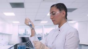 坐在桌上的一个女性化验员在一台膝上型计算机旁边在一个现代医学实验室审查蓝色的样品 影视素材