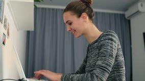 坐在桌上的一个少妇的侧视图,与快速地看屏幕的膝上型计算机和键入的文本一起使用和 股票录像