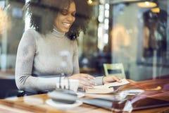 坐在桌上的一件灰色夹克的卷曲非裔美国人在现代咖啡店的窗口附近 免版税图库摄影