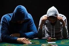 坐在桌上的两个专业打牌者 库存图片