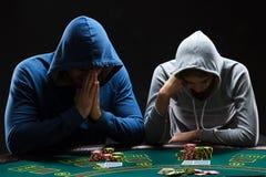 坐在桌上的两个专业打牌者 免版税图库摄影
