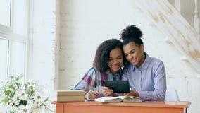 坐在桌上的两个可爱的卷发的混合的族种女孩获得乐趣,当吸取教训和使用片剂时 免版税图库摄影